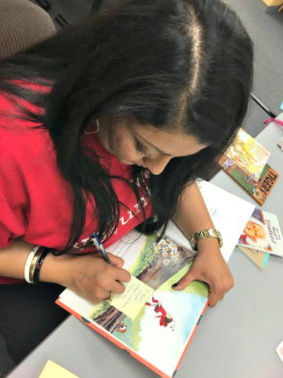 PHOTO: Adult woman in red shirt writes on a Post-It note attached to a children's book.
