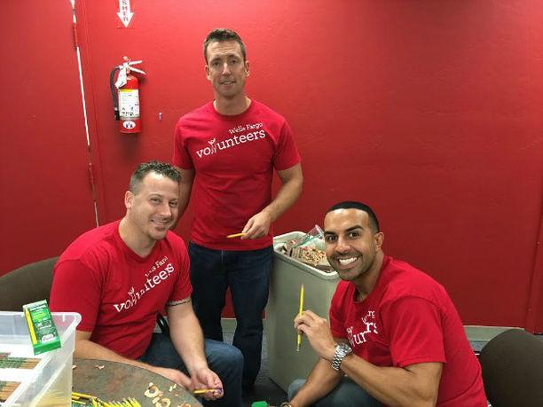 PHOTO: Three men wearing red shirts volunteer to sharpen pencils.
