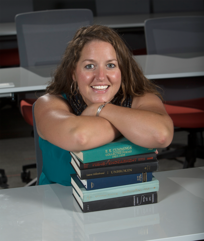 headshot of Sophie Etchart, leaning her arm on a stack of books