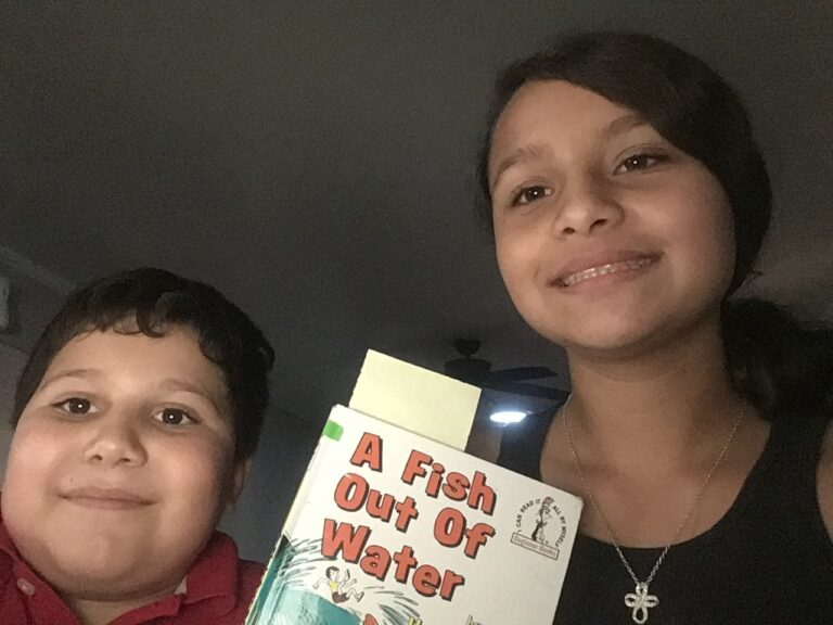 twos students smile and hold a book
