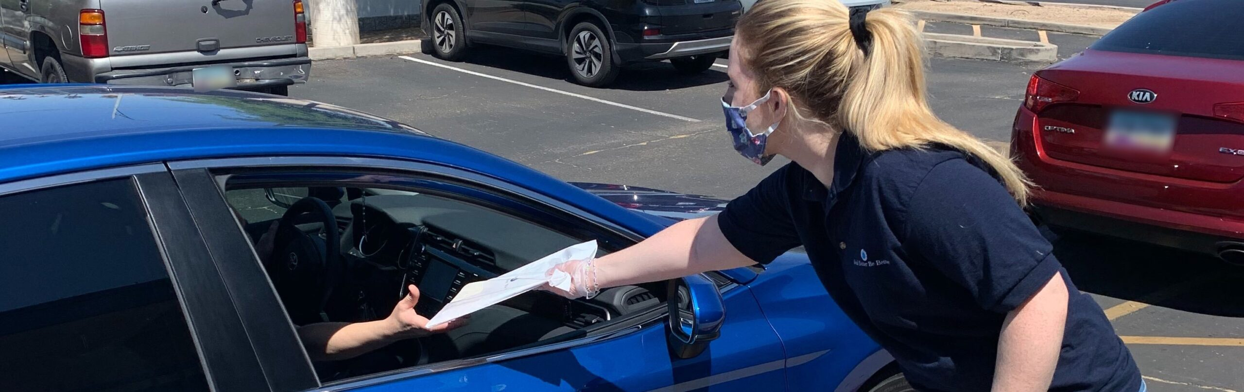 a Program Coach hands someone in a car a literacy kit