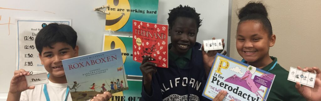 three students smile at the camera while holding up books