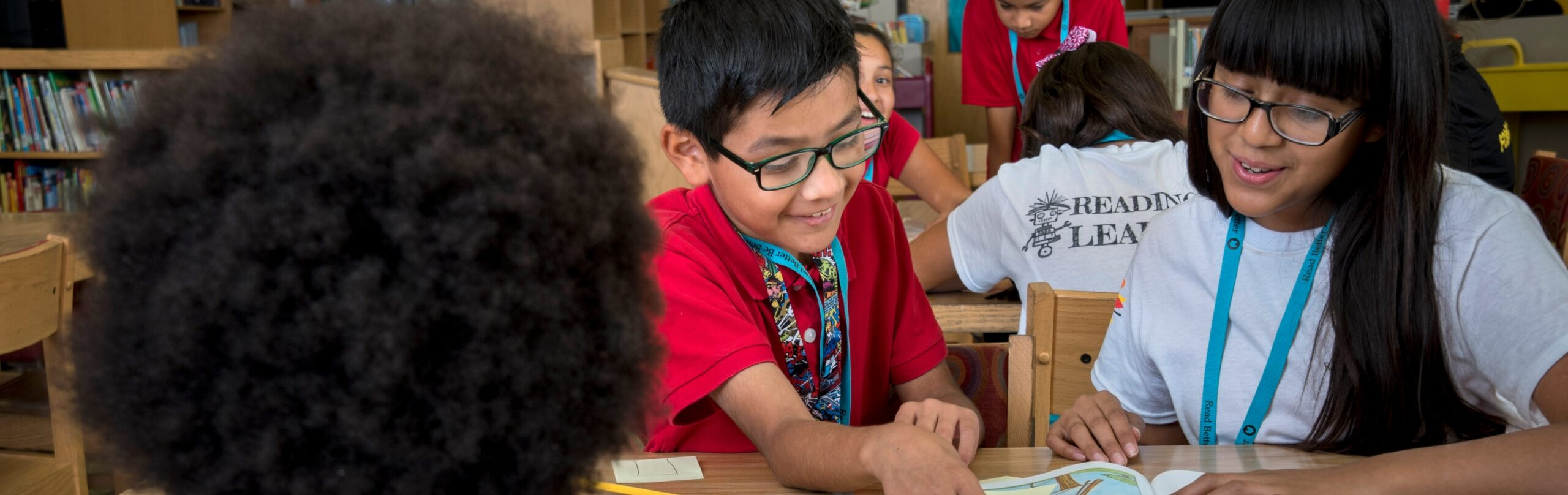 two students smiling and reading