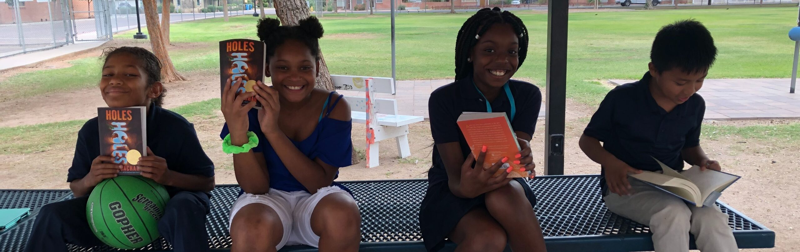 four students smile at the camera holding books