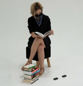 Molly Smithwick sits on top of a stack of books while reading a book