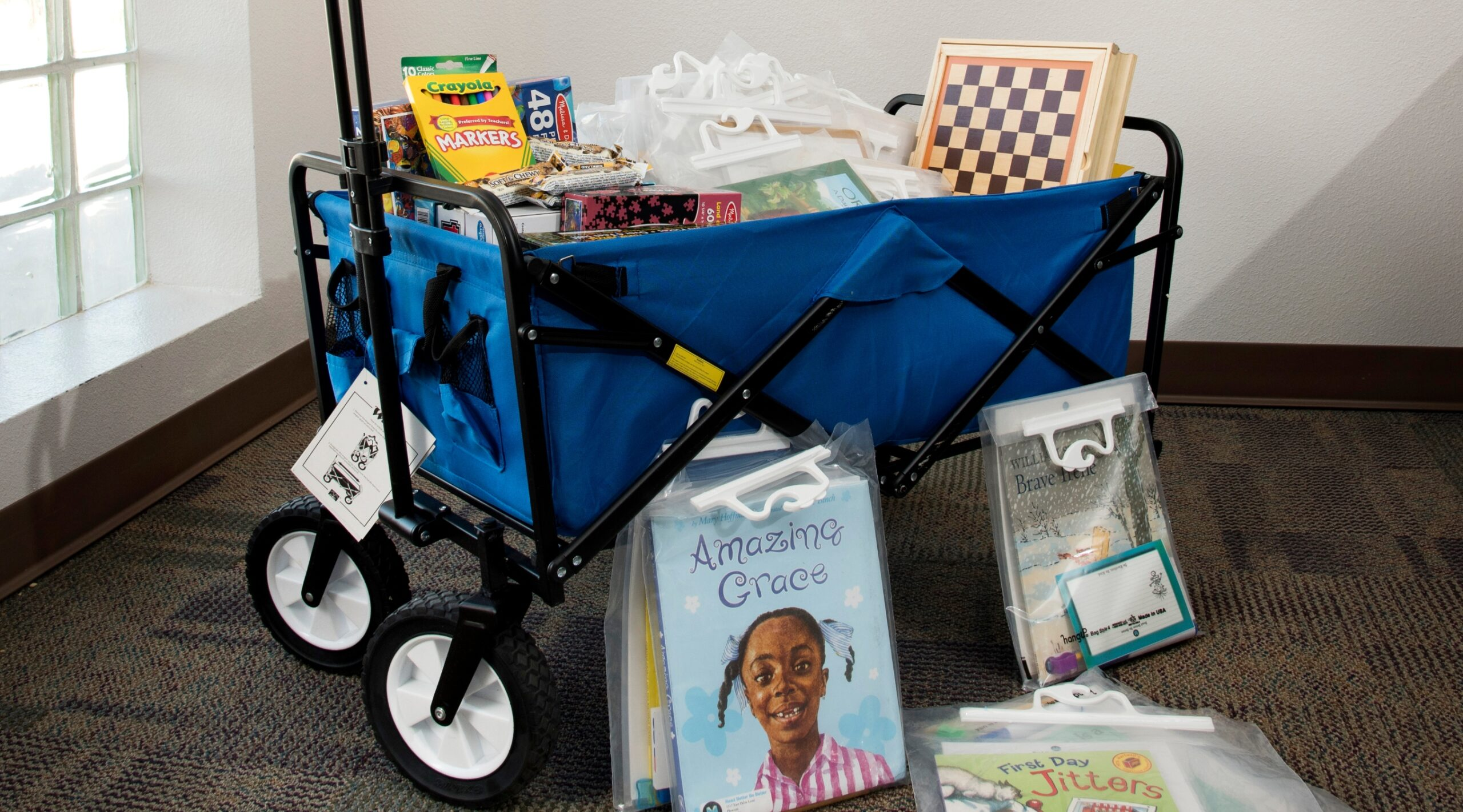 a wagon full of program materials: puzzles, games, and books