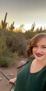 Shelby's full headshot, cacti and a sunset in the background